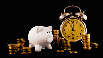 still life with clock, piggy bank, and stacked currency