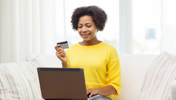 woman holding a debit card up while using a laptop computer